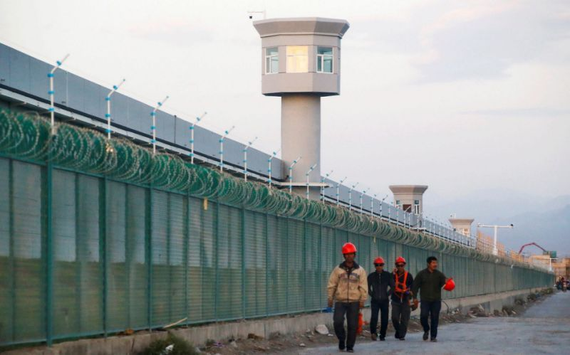 Workers walk by the perimeter fence of what is officially known as a vocational skills education centre in Xinjiang - REUTERS/Thomas Peter/File Photo