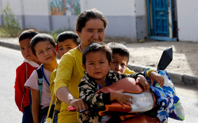 An Uighur woman and children sit on a motor-tricycle in western China's Xinjiang region - Andy Wong/AP
