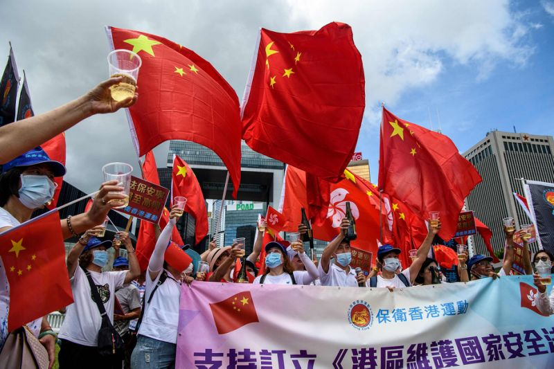 Image: Pro-China supporters display Chinese and Hong Kong flags as they raise a toast with champagne during a rally near the government headquarters in Hong Kong (Anthony Wallace / AFP - Getty Images)