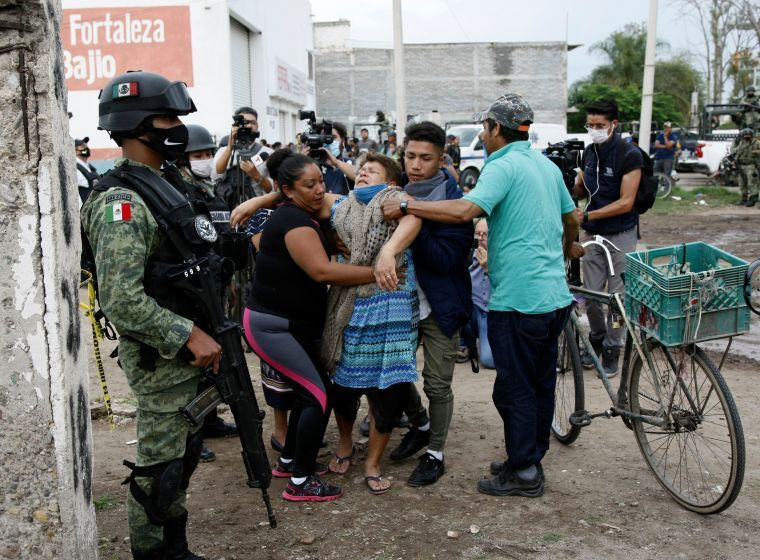 A woman reacts near the crime scene where 24 people were killed in Irapuato, Guanajuato state, Mexico, on July 1, 2020. - An armed attack at a drug rehabilitation center in Irapuato, a town in the central Mexican state of Guanajuato, left at least 24 dead and seven wounded on Wednesday, local authorities reported. (Photo by MARIO ARMAS / AFP) (Photo by MARIO ARMAS/AFP via Getty Images)