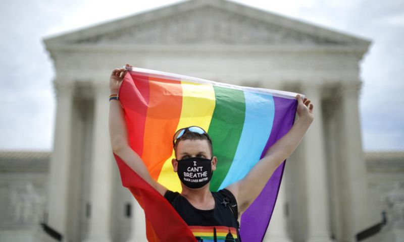 A demonstrator holds a Pride flag in front of the US supreme court building after the court ruled that LGBTQ people can not be disciplined or fired based on their sexual orientation.
