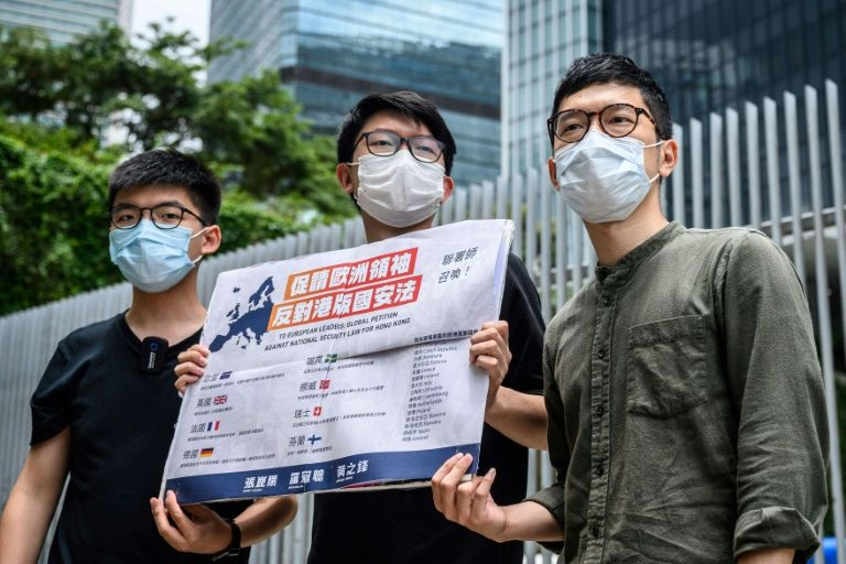 Hong Kong pro-democracy campaigner Nathan Law (far right) holds a placard urging European leaders to act against a national security law in June 2020 before he fled for Britain, where Beijing says Hong Kong police are seeking his arrest