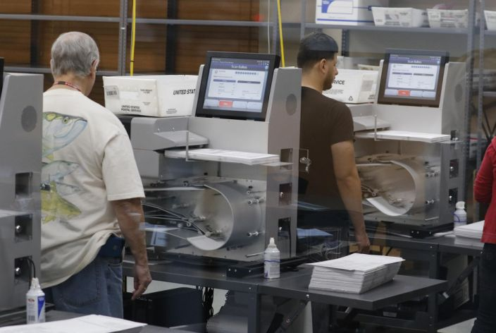 Florida elections staff load ballots into machines as the statewide vote recount is being conducted to determine the races for governor, Senate, and agriculture commissioner. (Joe Skipper/Getty Images)