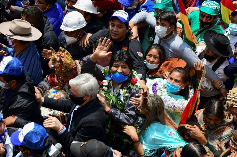 Bolivia's former president Evo Morales waves behind ex-vice-president Alvaro Garcia as he returns to Bolivia after a year in exile, with supporters greeting him in Villazon on November 9, 2020