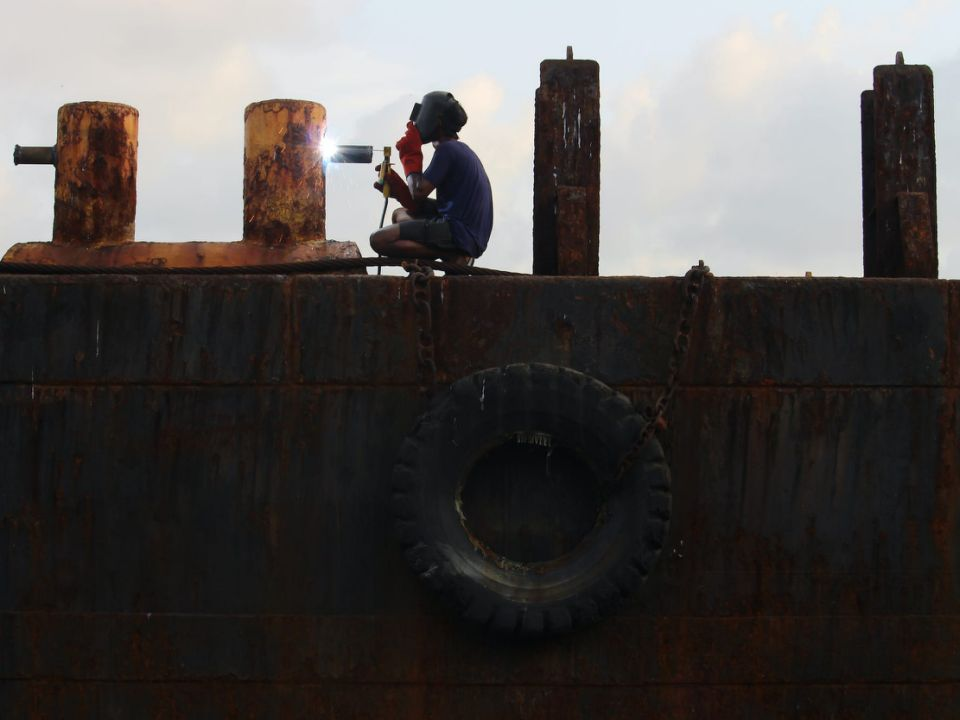 A worker welds part of a ship at a ship-breaking yard in Mumbai, India on 23 September 2019.