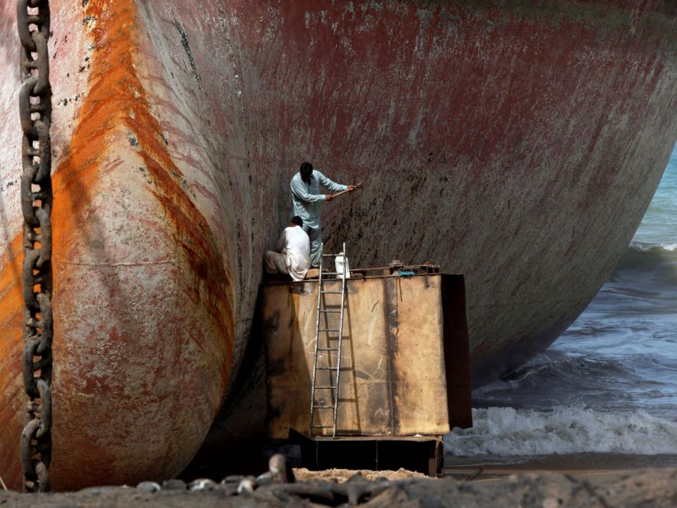 Labourers work without protective gear to separate parts of a ship for scrap metal at ship-breaking yard in Gadani, Baluchistan province