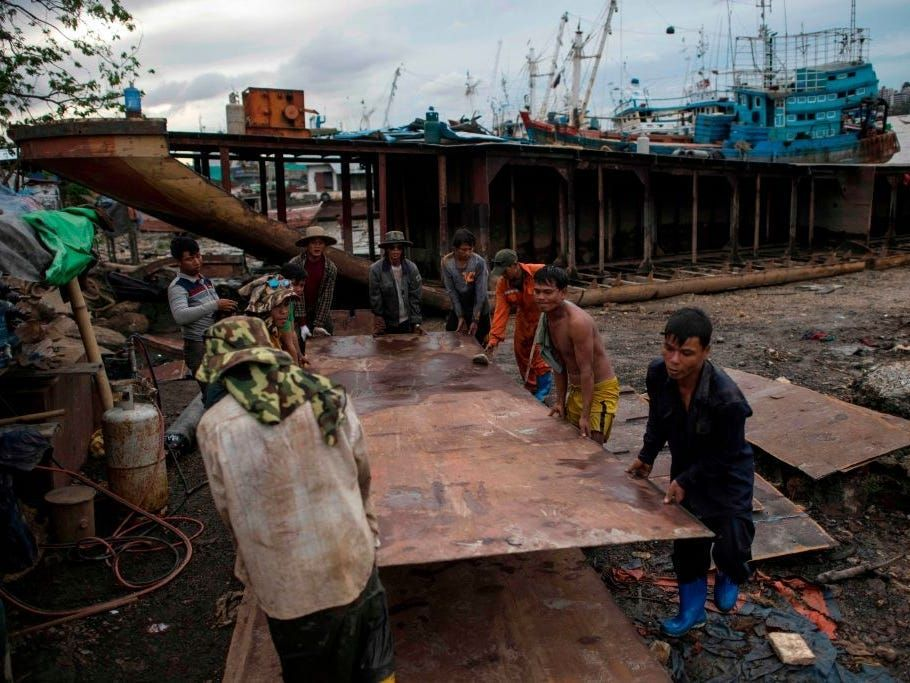 Workers carry a metal sheet dismantled from a ship at a ship-breaking yard on the bank of the Yangon River in Yangon on May 26, 2018.