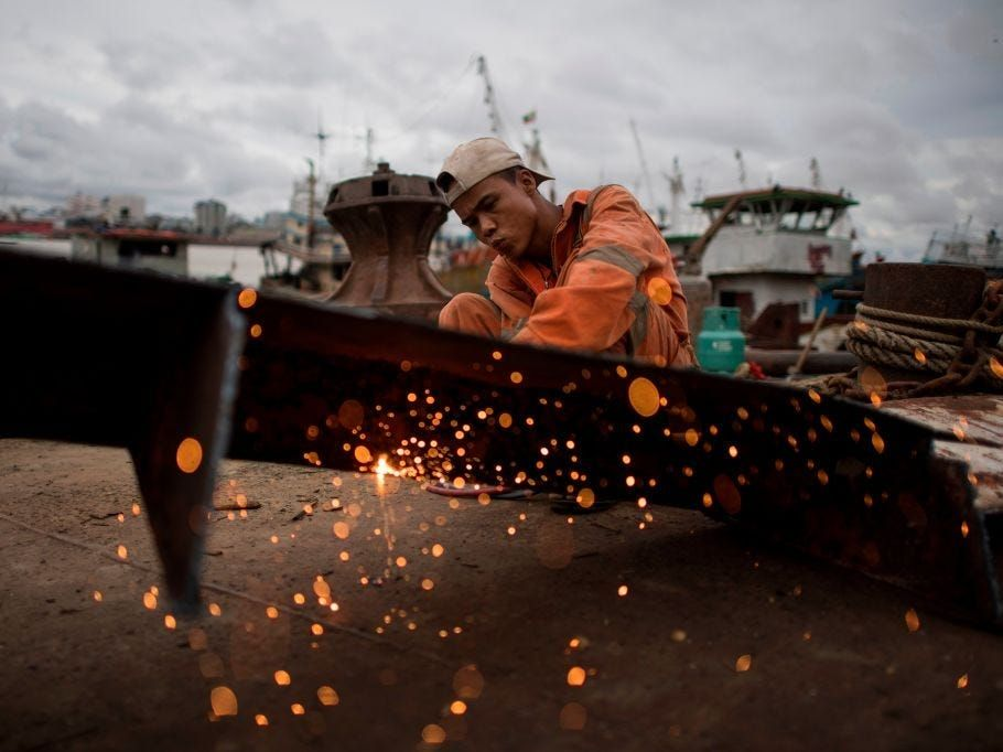 A worker uses a blowtorch to cut metal from a ship at a ship-breaking yard on the bank of the Yangon River in Yangon on May 26, 2018.