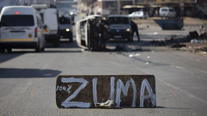 A burned car is seen at a road block during ongoing violent clashes in downtown Johannesburg, South Africa, 11 July 2021